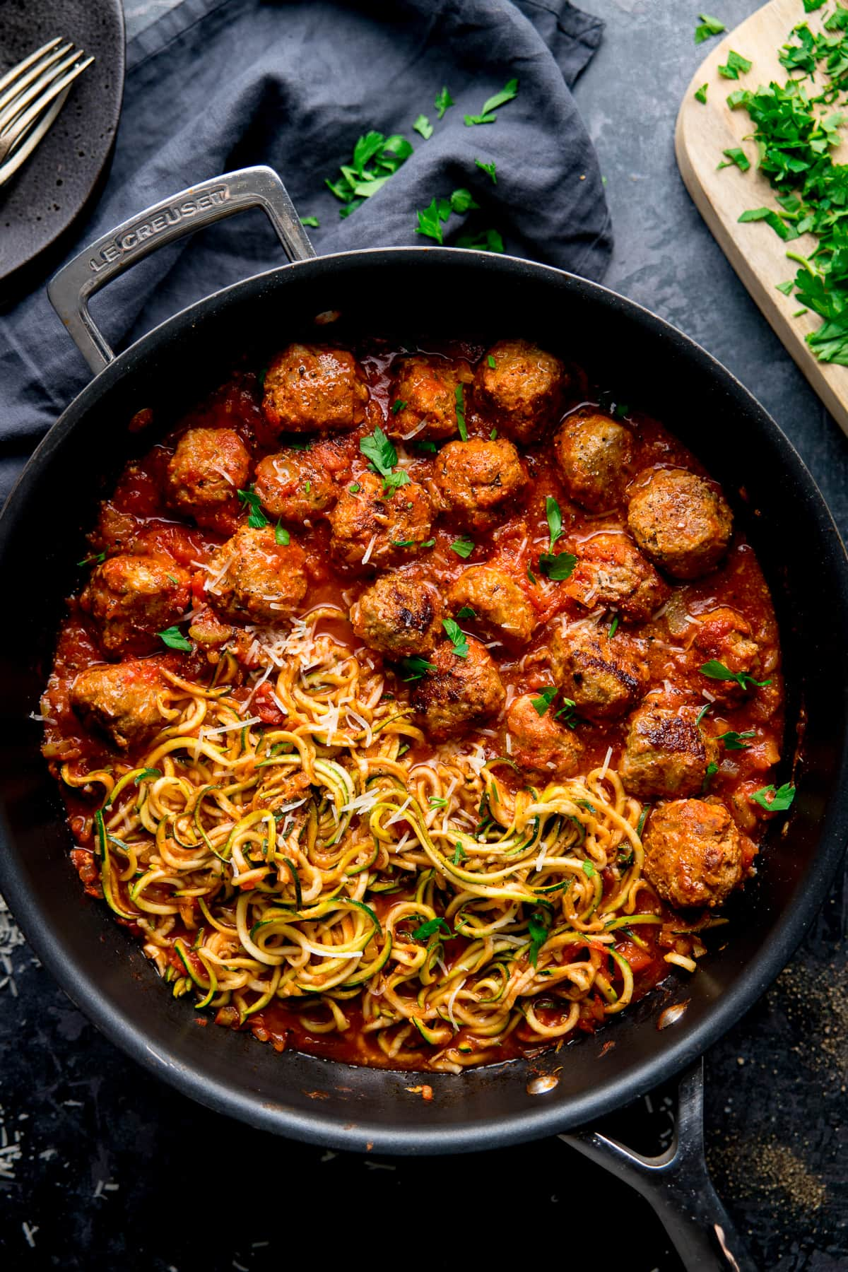 Turkey meatballs and courgetti in a pan topped with parsley, on a dark background.