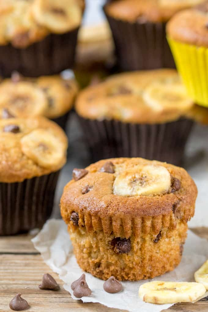 Close up picture of Light and fluffy Bakery Style Chocolate Chip Banana Muffins on grease proof paper