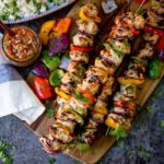 Square overhead shot of Mexican chicken kebabs piled on a wooden board. Salsa and rice in the background.
