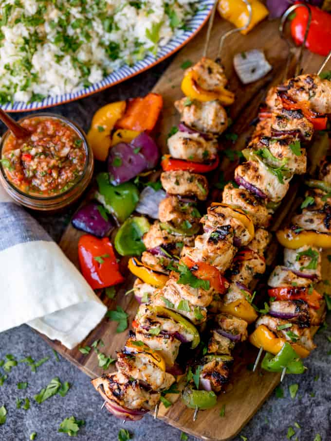 Mexican chicken kebabs piled on a wooden board. Salsa and rice in the background.