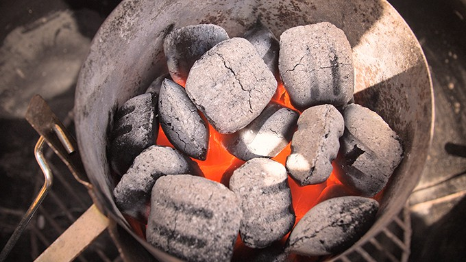 Hot coals in a barbecue chimney starter - heating up for a barbecue