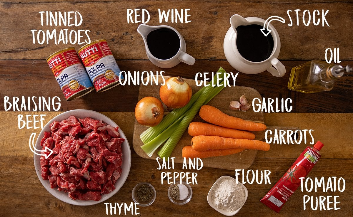 Ingredients for beef ragu on a wooden table