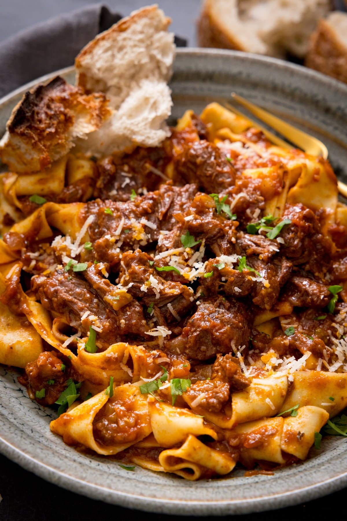 Beef ragu with pappardelle in a bowl with a chunk of bread.