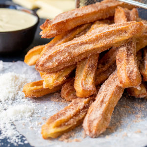 A pile of churros dusted with cinnamon sugar sat on their side.