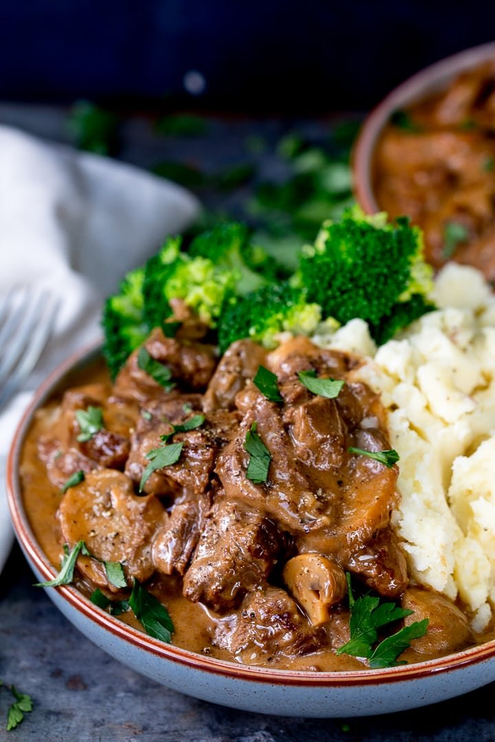 Side on photo of Slow Cooked Steak Diane Casserole in a bowl with Mash potato and broccoli