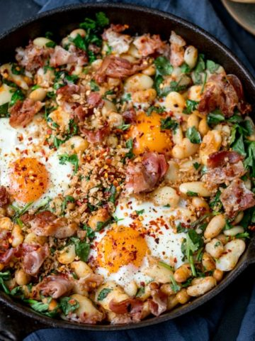 No, it's not shakshuka. Not a tomato in sight! This is my Spicy Egg Breakfast with Smashed Beans and Pancetta! A different way to serve your morning eggs! #onepan #brunch #bruncheggs #smashedbeans
