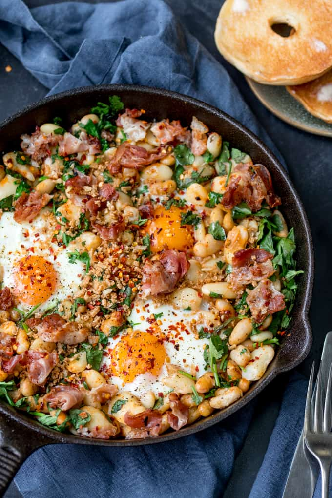 Overhead picture of  Spicy Egg Breakfast with Smashed Beans and Pancetta in a skillet
