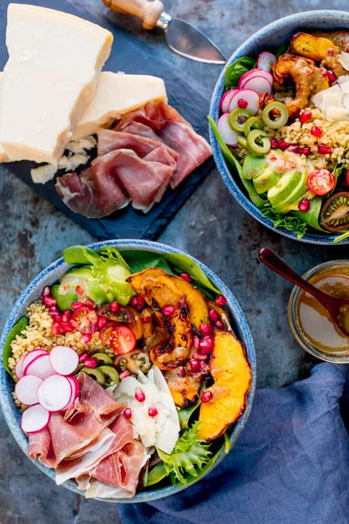 Overhead Photo of 2 bowls of Winter Nourish Bowl filled with goodies like roasted pumpkin, bulgur wheat and avocado with some Grana Padano and Prosciutto on a slate board