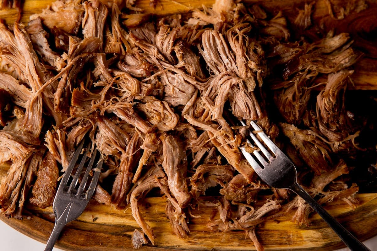 Shredded pork on a board with two forks