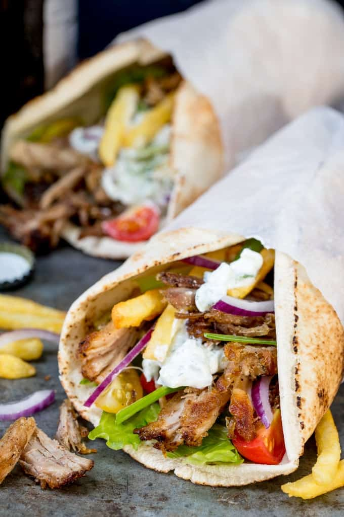 Pork Gyros in a flatbread with sauce and toppings, being held in a hand