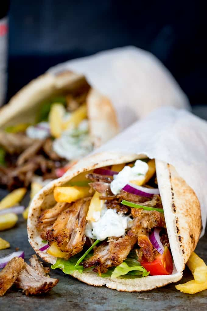 Pork gyros on an open flatbread with lettuce, onion, tomato and tzatziki