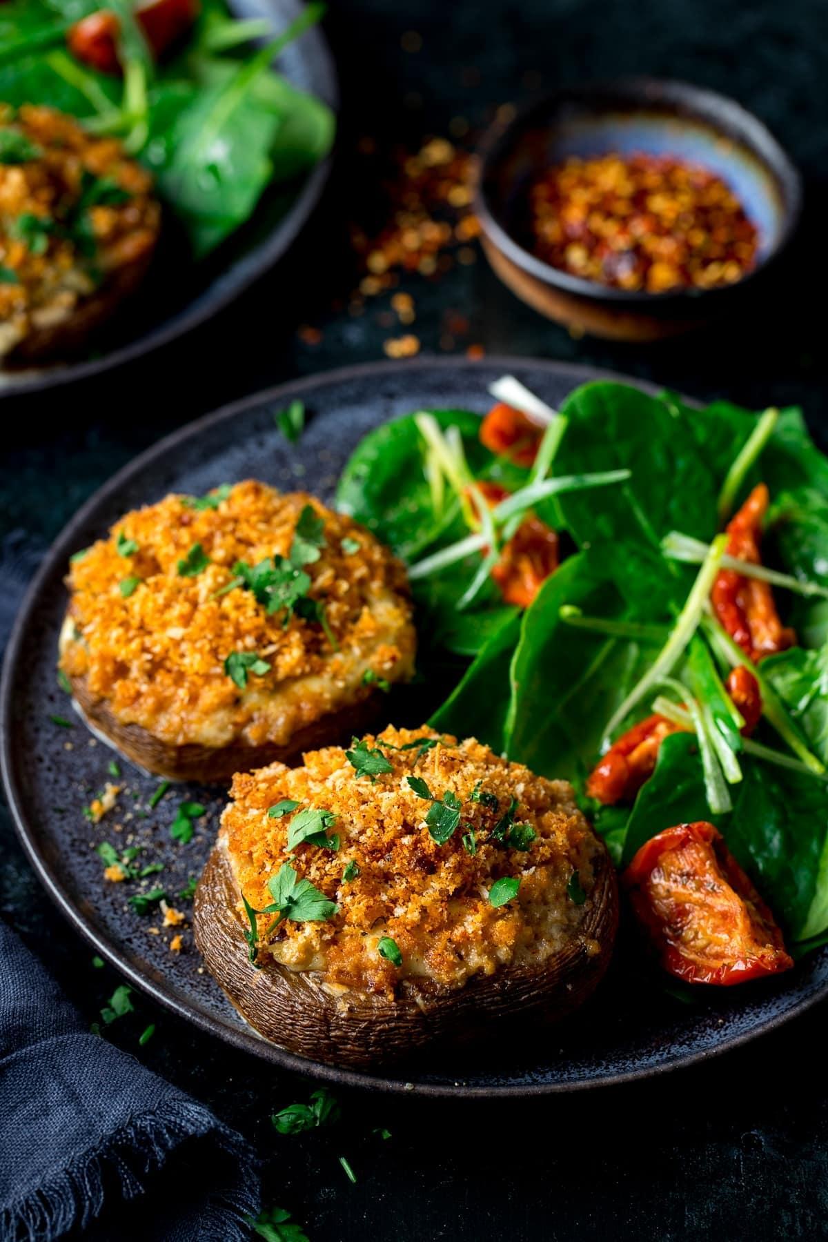 Stuffed mushrooms with salad on a dark plate