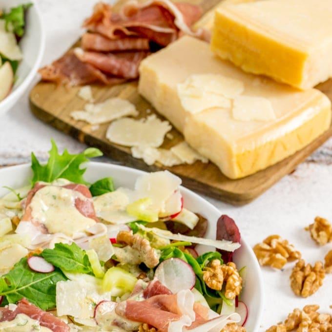 Close up photo of Fennel and Apple Winter Salad with Grana Padano and Prosciutto Di San Daniele in the background