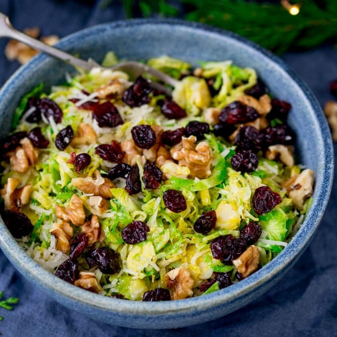 Square image of a bowl with shaved sprouts topped with cranberries, walnuts and parmesan in a honey mustard dressing