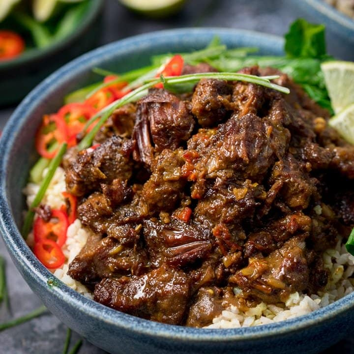 Beef rendang in a blue bowl with rice, chillies and greens
