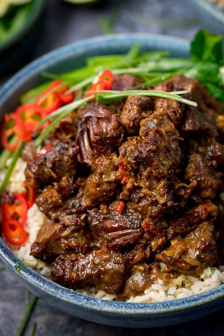 Beef rendang in a blue bowl with rice and chillies