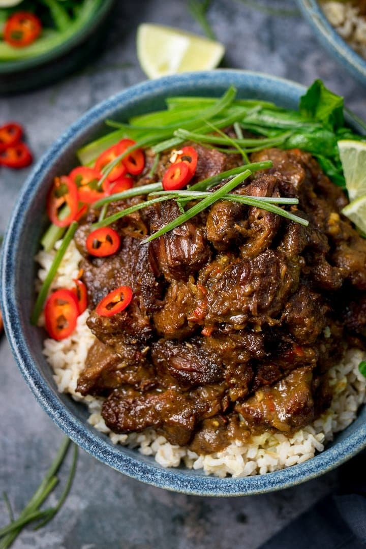 Overhead image of Beef rendang in a blue bowl on rice