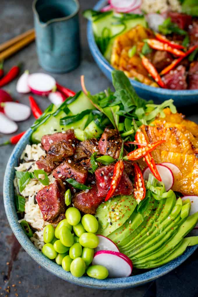 Steak poke bowl with avocado and pineapple in a blue bowl