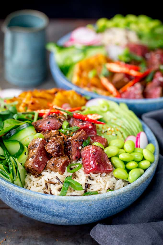 Side on shot of steak poke bowl with rice, cucumber and edamame in a blue bowl. Further poke bowl in the background.