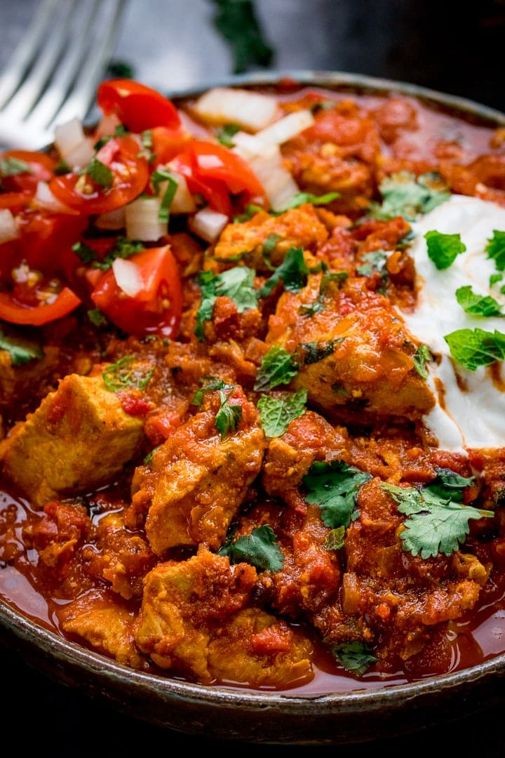 Overhead photo of Spicy Chicken Rogan Josh with soured cream and a bowl of chopped tomatoes and onions