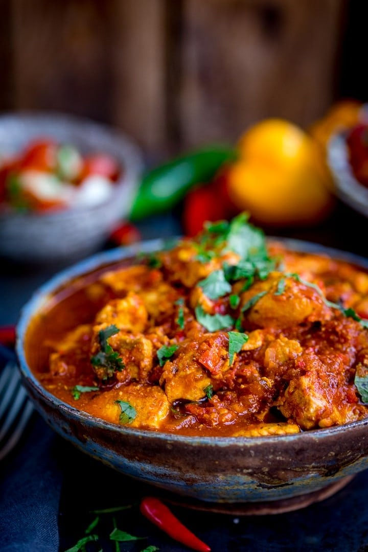 Close up photo of Healthier Slow Cooked Spicy Chicken Rogan Josh in a stone bowl on a blue board with chilli peppers in the background