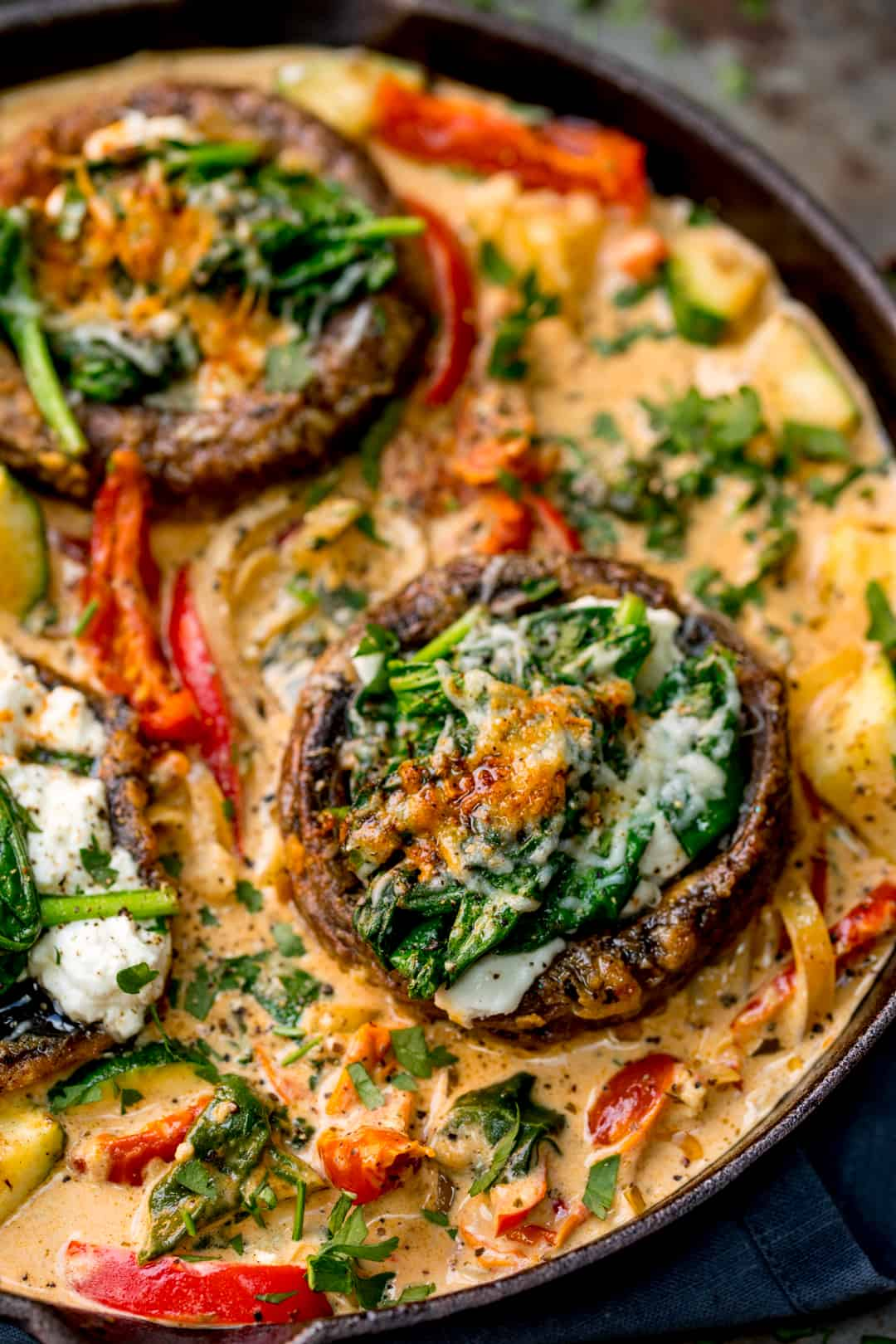Overhead close up of Tuscan Style Stuffed Mushrooms in Creamy Sun Dried Tomato Sauce in a skillet
