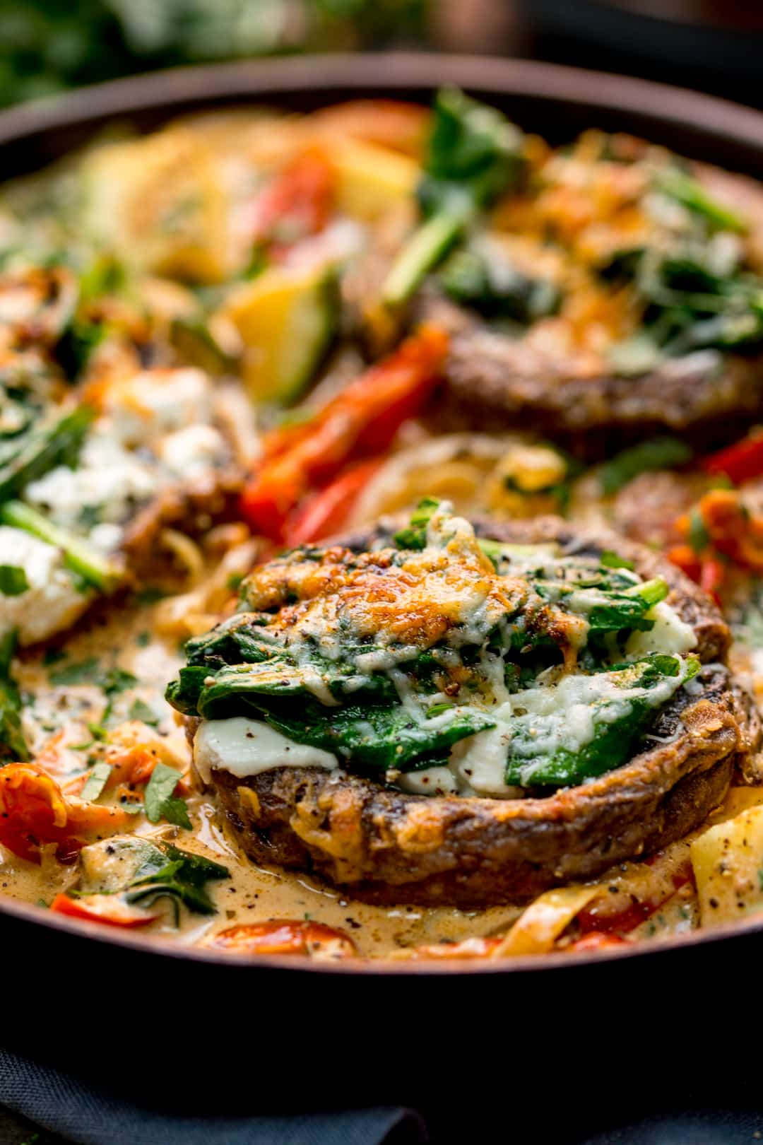 Extreme close up of Tuscan Style Stuffed Mushrooms in Creamy Sun Dried Tomato Sauce in a skillet