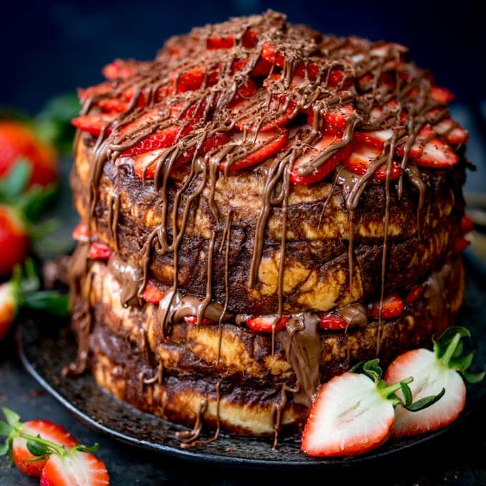 Close up image of a four layer chocolate bread and butter pudding round cake on a black plate. Nutella and strawberries on the top and in the middle. Dark blue background, strawberries scattered around.