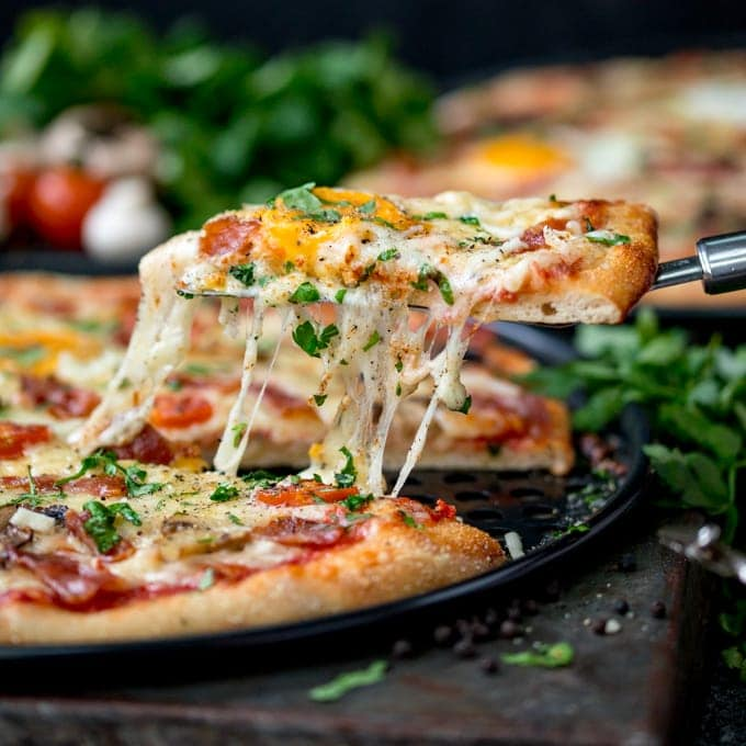 Side-on image of egg-topped breakfast pizza slice being lifted from the pizza. Melted cheese is stretching between the pizza and pizza slice.