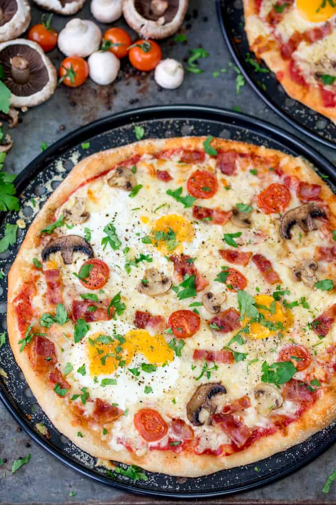 Slightly cut off image of breakfast pizza with eggs, bacon, tomatoes and mushrooms. Uncut mushrooms, tomatoes and parsley in the background.