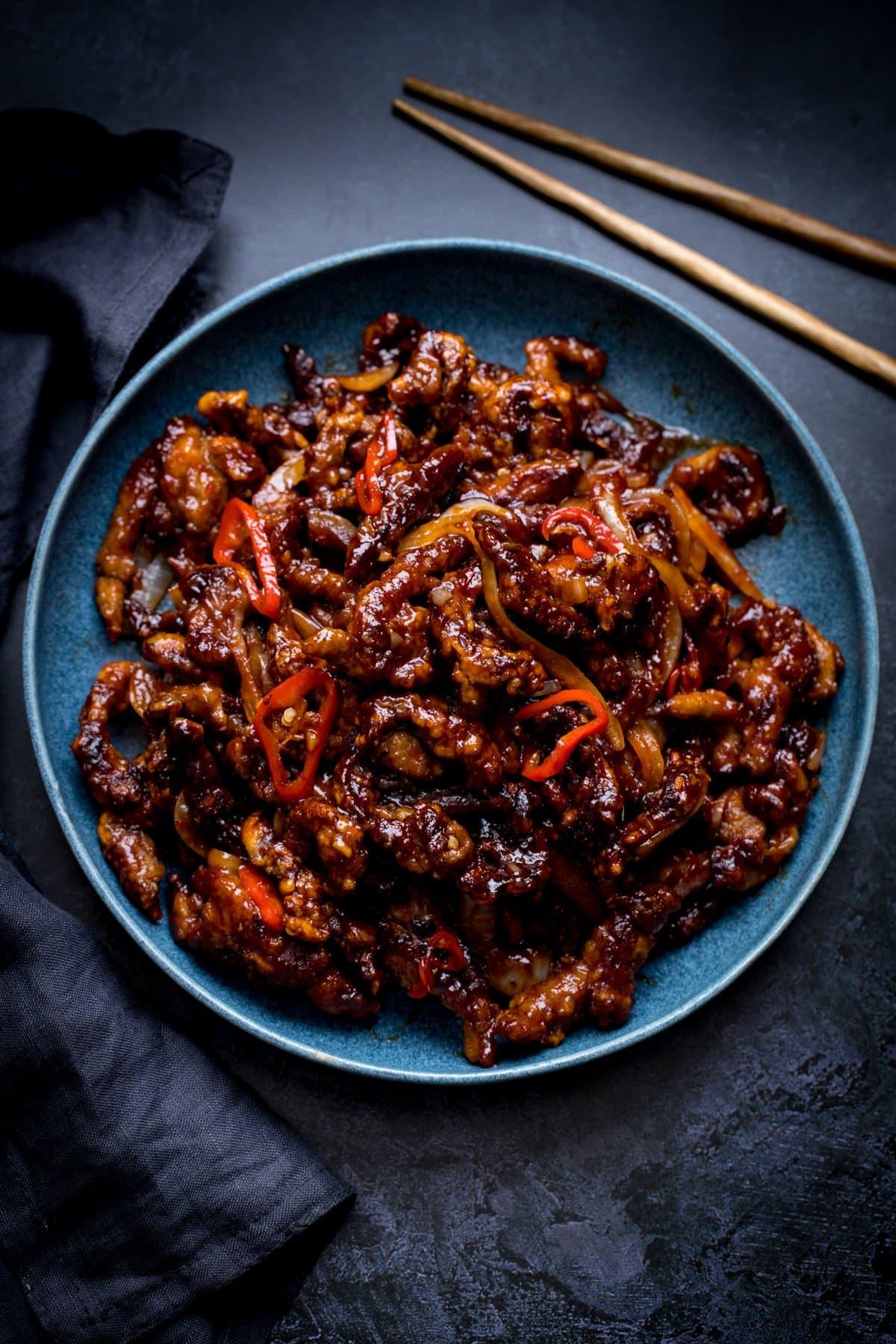 crispy chilli beef in a blue bowl on a dark background. Dark napkin and set of chopsticks also in shot.