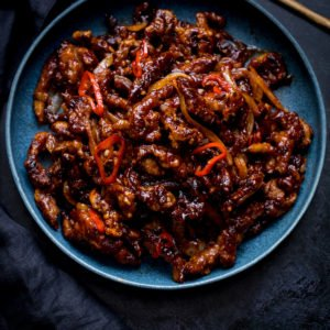 Square image of crispy chilli beef in a blue bowl