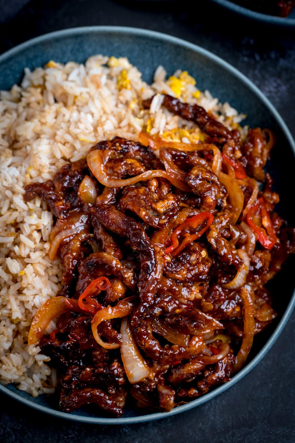 crispy chilli beef in a blue bowl with egg fried rice