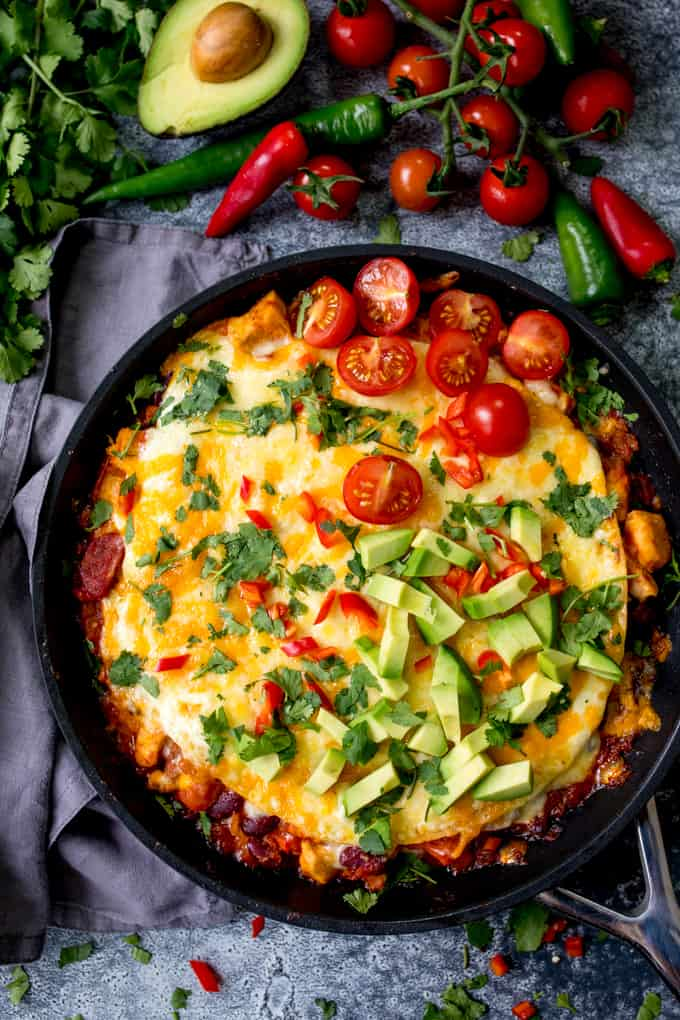 Overhead photo of chicken enchilada lasagna in a pan, topped with avocado, tomatoes and chopped chillies.