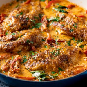 Creamy Tuscan Chicken in a dark pan