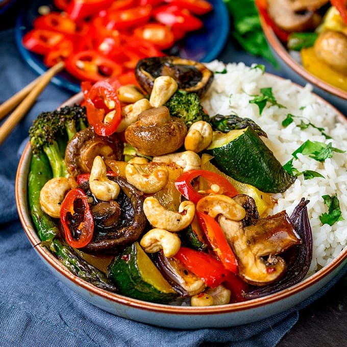 Bowl of vegetables in asian-style sauce with rice, cashew nuts and chopped chillies.