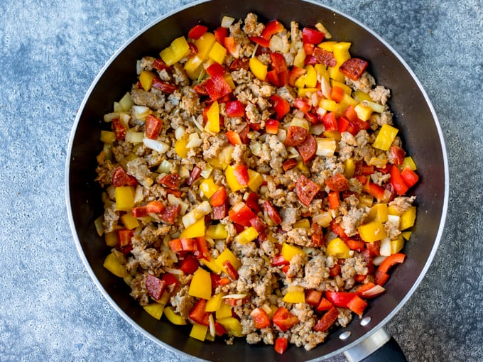 Ground sausage, chorizo, onions and peppers in a pan