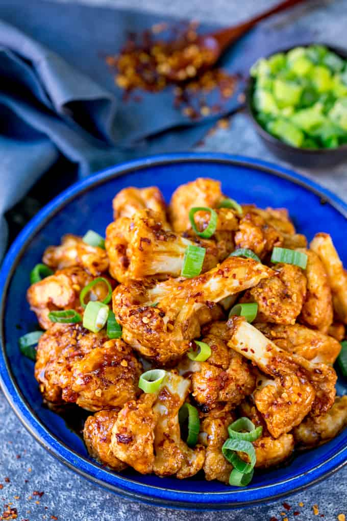 Asian cauliflower wings on a blue plate with spring onions sprinkled on top