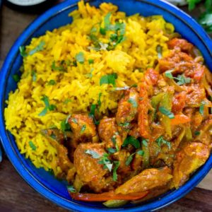 Overhead shot of chicken jalfrezi and pilau rice in blue bowl.