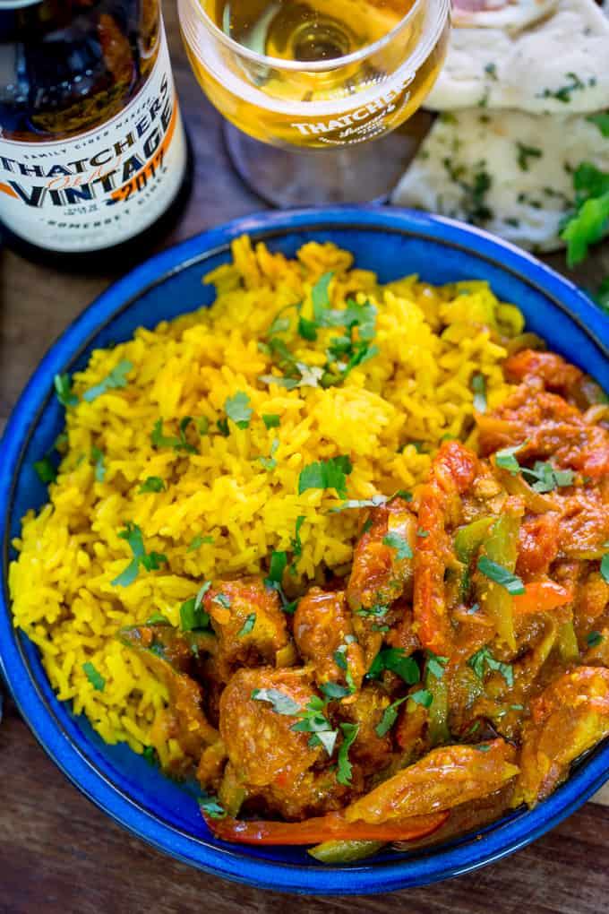 Homemade chicken jalfrezi with pilau rice in a blue bowl.