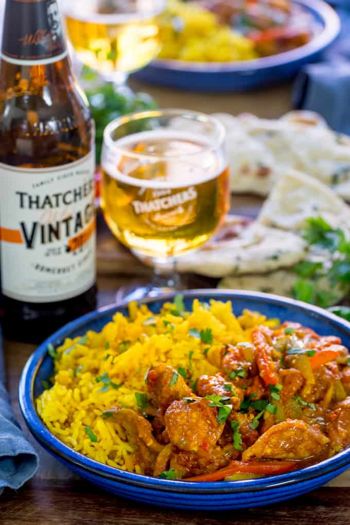 Homemade chicken jalfrezi with pilau rice in a blue bowl. Glass of cider and a bottle of cider in the background.