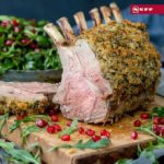 Herb crusted rack of lamb on a wooden board with a slice taken off - showing pink centre. Rocket and pomegranate seeds strewn around the board.