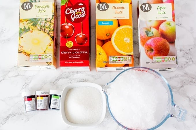 Ingredients for fruit snow cones. These are 4 different fruit juice cartons, ice, sugar, food colouring gel