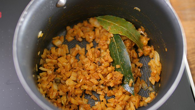 spices and onions sauting in a saucepan for pilau rice