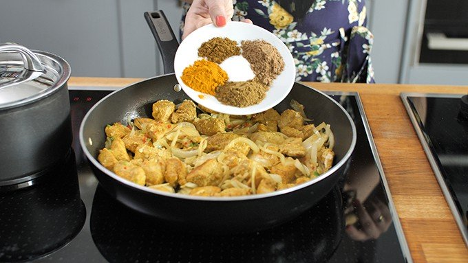 spices being added to a pan with chicken and onions