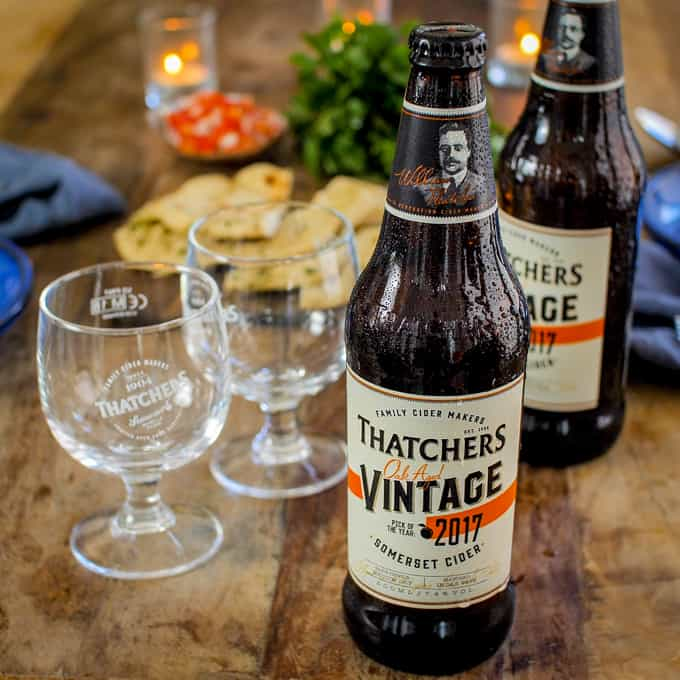 2 bottles of thatchers vintage cider on a rustic wooden table with 2 glasses