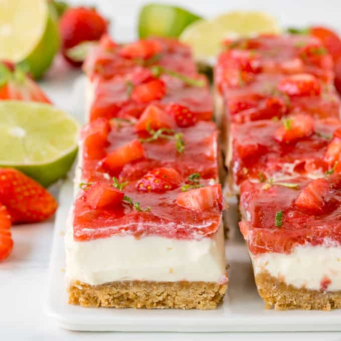 Square image of strawberry and rhubarb cheesecake bars with jelly topping and lime zest sprinkled on top
