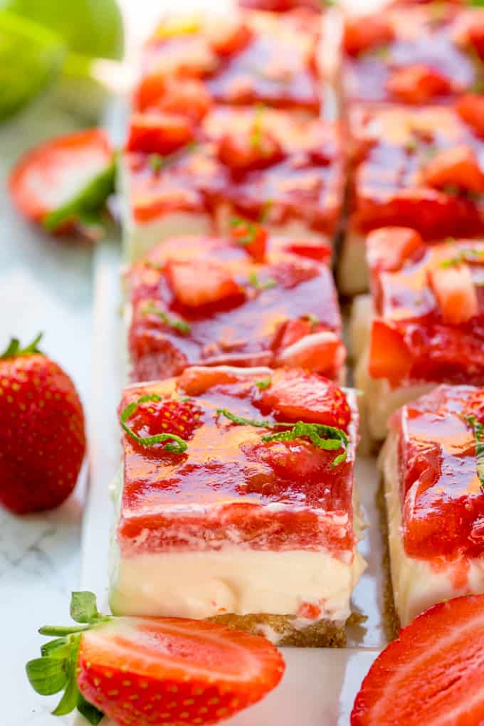 Tall image of strawberry and rhubarb cheesecake bars with jelly topping. Strawberries scattered around.