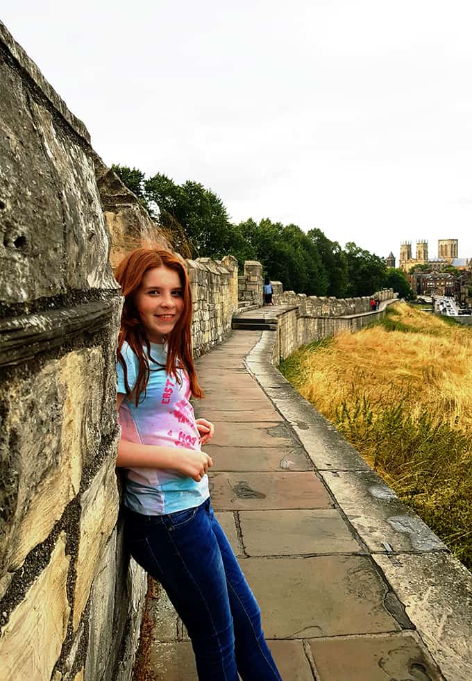 My daughter standing on the city walls in York