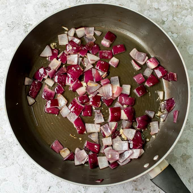 Red onion pieces cooking in pan